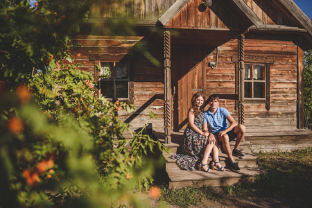 Couple men and women in the village, near a wooden house. Country style. Rustic summer