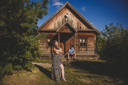 Loving romantic couple in the village, near a wooden house. A man sits on the porch, a young woman in the foreground. Concept: love, romance, summer