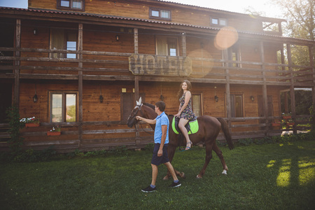 Romantic young couple in love, a walk on a horse on nature background and wooden country-style hotel. Young woman sitting on horseback. A man walks around, holds . Concept: love, romance, Hobbies.