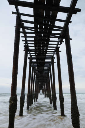 bridging the gap: Wooden Bridge on the beach with waves and refection - vertical image