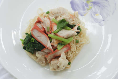 Delicious Asian egg noodles with barbecued red pork, dumplings and vegetables   photo