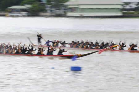 panning shot: Bangkok, Thailand - August 25,2013 - Two rowing teams in full speed during Thai Long-tailed Boat Competition along Chaopraya river at Rama 8 Bridge