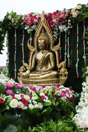 Buddha image and flowers in the annual Buddhist lent candle festival parade photo