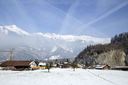 Small town and snow covered mountain in winter, Switzerland photo