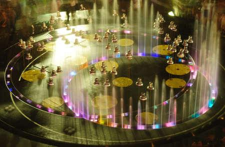 Fuente de agua colorida en la noche con las campanas de la decoración Foto de archivo - 22874387