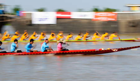 paddler: Pathumthani, Thailand - NOV 03, 2013  Panning shot of two rowing teams in full speed during Thai Long-tailed Boat Competition along river
