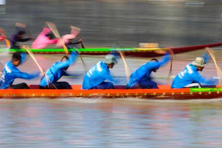 panning shot: Pathumthani, Thailandia - 3 novembre 2013 Panning tiro di due squadre di canottaggio in piena velocit� durante Thai coda lunga barca Concorso lungo il fiume a Samkhok, Pathumthani, Thailandia