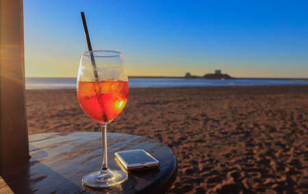 a glass of spritz in front of a beautiful sunset