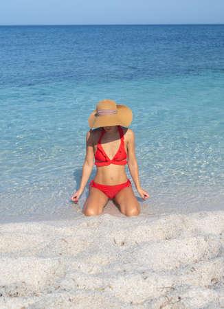 Happy woman enjoying the beach relaxing joyful in the summer by the tropical blue water. Beautiful happy bikini model traveling wearing sun hat on is arutas beach, Sardinia, Italy Archivio Fotografico