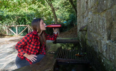 girl fills a bottle of water and quenched her thirst in a spring of water in the high mountains