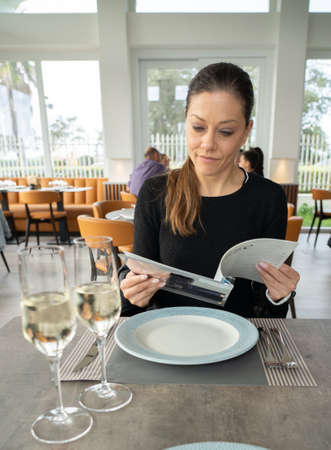 woman reading the menu in restaurant
