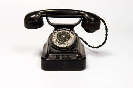 A phone with a rotary dialer on a white background with a wired phone Stock Photo