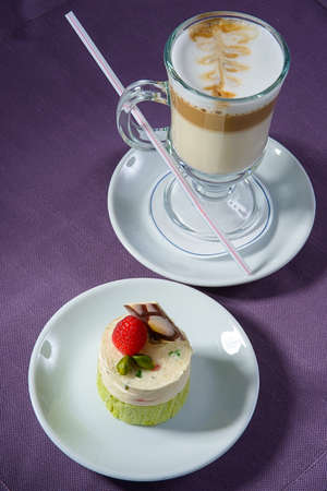 Strawberry romantic dessert with a coffee drink in a glass mug on a purple napkin