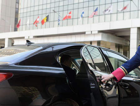 the doorman opens the door of a luxury car near the hotel, business class
