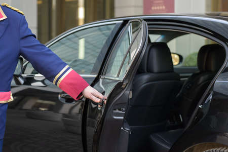 ドアマンはホテルは、ビジネス クラスの高級車のドアを開ける