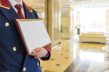 the doorman in the lobby of the hotel holding a sign Banco de Imagens - 74209648