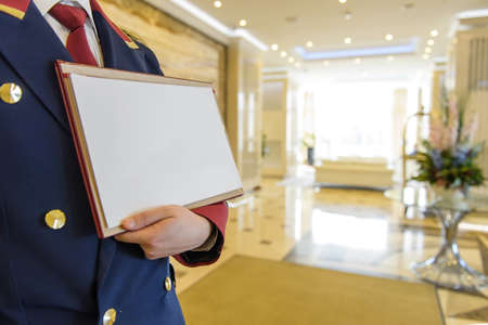 the doorman in the lobby of the hotel holding a sign