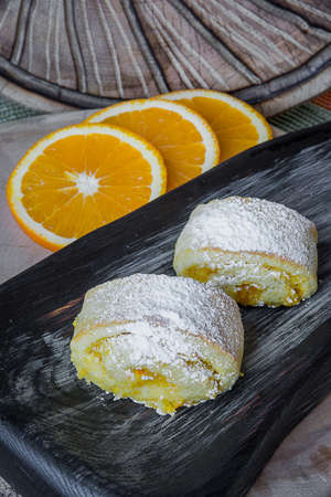 Orange rolls on a textured cutting Board from under oranges with powdered sugar Banco de Imagens - 75781472