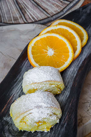 Orange rolls on a textured cutting Board from under oranges with powdered sugar Banco de Imagens - 75781476