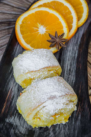 Orange rolls on a textured cutting Board from under oranges with powdered sugar Banco de Imagens