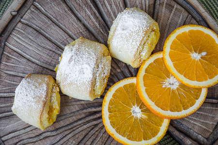 Orange rolls on a textured cutting Board from under oranges with powdered sugar Banco de Imagens - 75781475