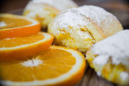 Orange rolls on a textured cutting Board from under oranges with powdered sugar Banco de Imagens - 74967075