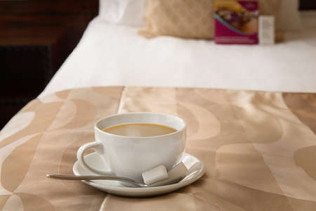 Cup of coffee on a metal tray on the bed with a small spoon and two sugars