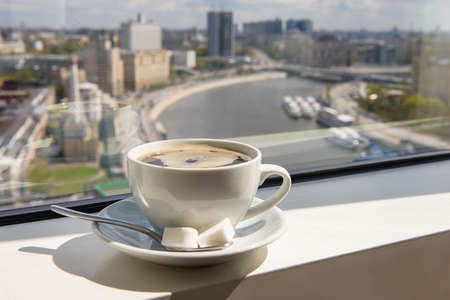 Cup of coffee on the windowsill in a tall building overlooking the city from the river Banco de Imagens