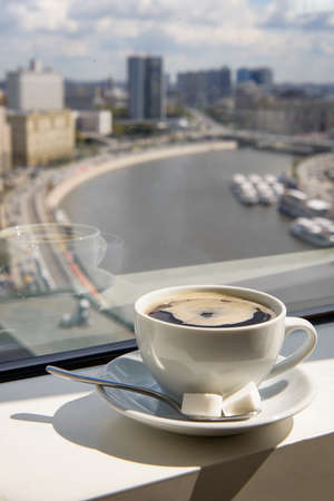 Cup of coffee on the windowsill in a tall building overlooking the city from the river Banco de Imagens - 78432168