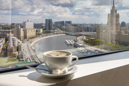 Cup of coffee on the windowsill in a tall building overlooking the city from the river Banco de Imagens - 78432169