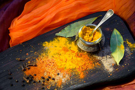 Turmeric with spices in a pepper pot on textured wooden Board in Oriental style