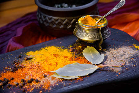 Turmeric with spices in a pepper pot on textured wooden Board in Oriental style Banco de Imagens - 79329664