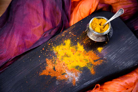 Turmeric with spices in a pepper pot on textured wooden Board in Oriental style Banco de Imagens - 79329656