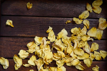 Yellow dried rose petals on wooden boards brown color