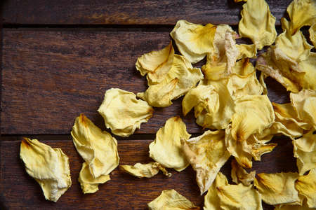 Yellow dried rose petals on wooden boards brown color Banco de Imagens - 87004935
