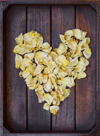 Yellow dried rose petals on wooden boards brown color Banco de Imagens - 86671529