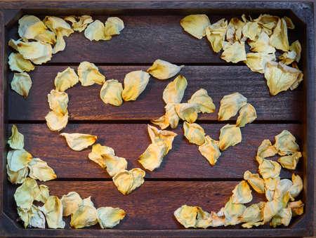 Yellow dried rose petals on wooden boards brown color Banco de Imagens - 87004937