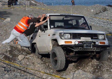 Off-road vehicle in difficulty during a winter race on the beach of the village of Cogoleto in Italy.