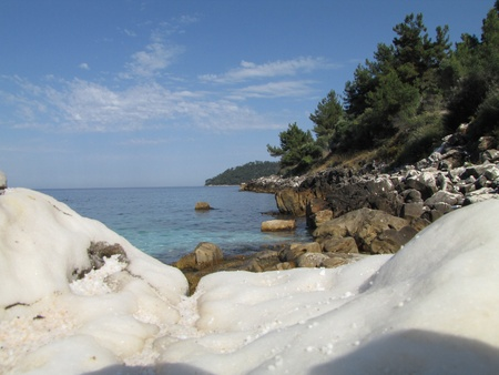 white marble rock, blue water and green pine on Marble or Saliara beach, Thassos, Greece photo