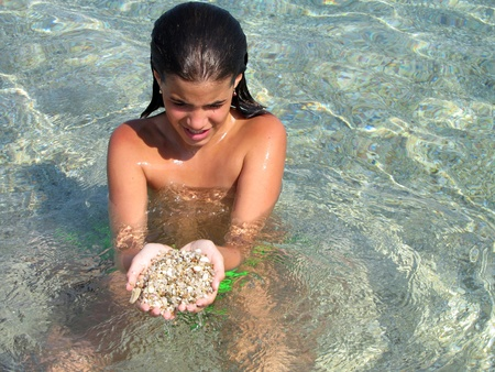 Little girl in sea shoal with hands full of pebble
