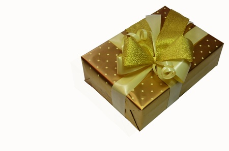 Wrapped gift box with golden ribbon bow, isolated on white photo