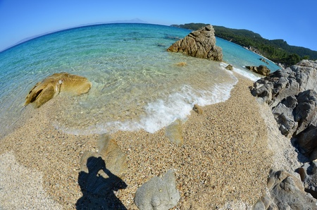 Seascape fisheye view with a huge stones and Mt Atos in the distance, Fava beach, Chalkidiki, Sithonia, Greece photo