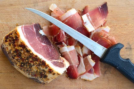 Homemade spicy prosciutto, smoked and dried in the wind for a long time on wooden chopping board with long, thin knife, view from above photo