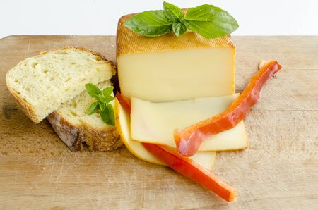 Smoked full fat cheese, a couple of slices and piece, healthy homemade bread, fresh red pepper and fresh, green basil leaves on grunge wooden chopping board photo