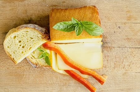 Smoked full fat cheese, a couple of slices and piece, healthy homemade bread, fresh red pepper and fresh, green basil leaves on grunge wooden chopping board, view from above photo