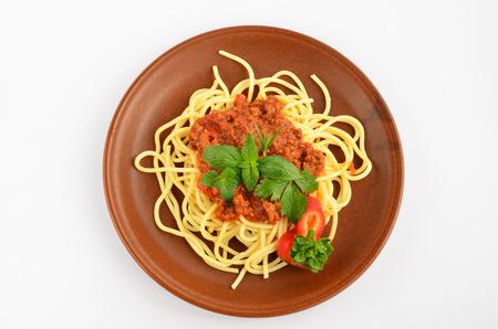 vista superior: Spaghetti Bolognese con especias de hierbas frescas - or�gano, la albahaca, el romero, el apio y el pimiento rojo, servido en un plato de cer�mica r�stica, de color marr�n sobre fondo blanco Foto de archivo