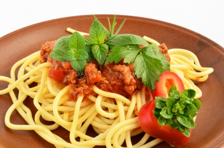 Spaghetti Bolognese with fresh herb spices - oregano, basil, rosemary, celery and red pepper, served on rustic, brown ceramic plate over white background photo