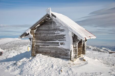 Small log house on the very peak of the mountain, a shelter for the ski lift staff and visitors, Mt Kopaonik  photo