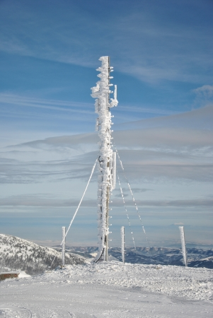 polar station: Telecommunication antenna on the top of the mountain, frozen and completely covered by snow and icicles against blue sky with some high clouds