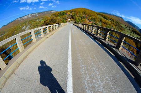 Bridge over the Tara river canyon, fisheye landscape with pfotographer shadow photo